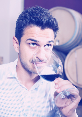 Glad man holding glass of red wine in winery section in store Stock Photo