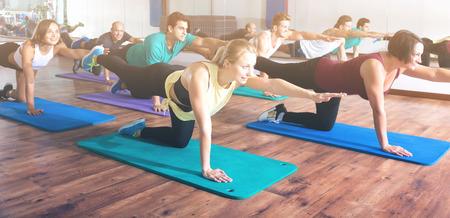 adult learners: adultos alegre que tiene clase de yoga en club de deporte Foto de archivo
