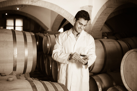 taster: smiling professional taster of winery posing with wine in cellar Stock Photo