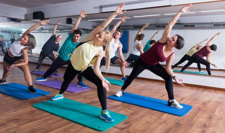 position d amour: Sourire hommes et dames américaines d'apprentissage des positions de yoga Banque d'images
