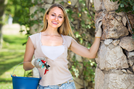 horticultural: positive young woman holding horticultural tools in garden on sunny day
