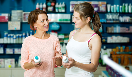 buying questions: Cheerful woman with daughter teenager shopping healthcare products in drug store Stock Photo