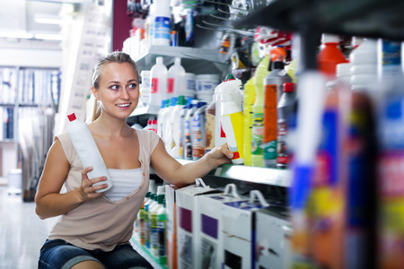 housewares: Portrait of young female customer taking bottle with paint thinner in housewares department