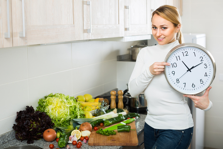 checking ingredients: Smiling young housewife cooking vegetables and checking time on the clock at home kitchen Stock Photo