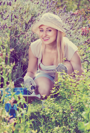 horticultural: Happy young blond smiling woman working in garden using horticultural instruments on summer day