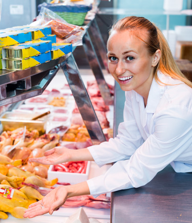 cheerful young woman wearing uniform selling fresh chicken carcass in delicatessen section Stock Photo