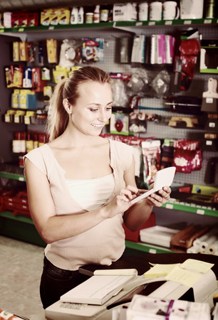 housewares: portrait of young positive woman at cash desk in tool-ware shop