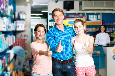 Family with girl teenager holding thumbs up in pharmaceutical store Stock Photo