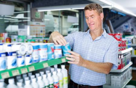 thoughtful man customer choosing paint bucket in housewares hypermarket