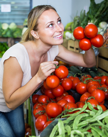 cheerful young woman choosing fresh ripe tomatoes on market Stock Photo