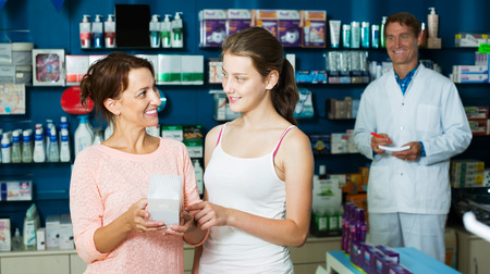 buying questions: Happy mother with teenager daughter choosing healthcare products in drug store