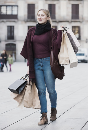 Smiling young blond woman holding shopping paper bags at the street