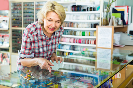 Mature smiling woman choosing sewing supplies in glass showcase in boutique Stock Photo