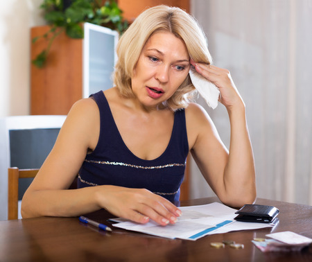 Sad elderly woman filling in financial documents at table in home