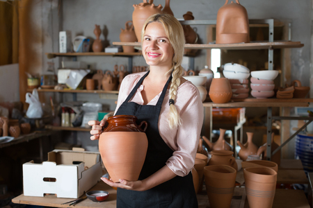 atelier: Smiling woman potter in apron carrying ceramic vessels in atelier Stock Photo