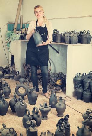 atelier: cheerful female artisan with black-glazed ceramic vases in atelier Stock Photo