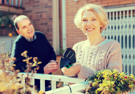 Smiling aged woman with horticultural sundry and aged man drinking tea in patio Stock Photo