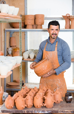 positive american man potter holding ceramic vessels in atelier Stock Photo