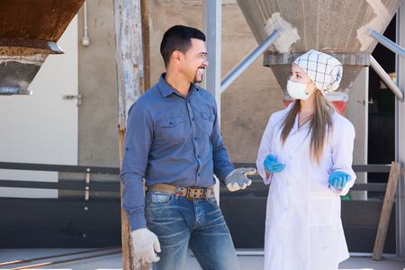 protective clothing: Smiling male farmer and female veterinarian in protective clothing standing in sty