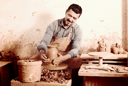atelier: Portrait of glad male potter working with clay on pottery wheel in atelier