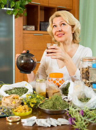Mature woman sitting at table with aroma herbs and smiling