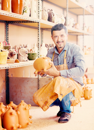 workroom: Happy male artisan holding ceramics in hands and standing in workroom