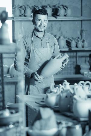 faience: Happy male artisan having ceramics in hands and standing in ceramics studio
