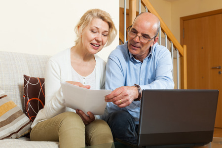 Smiling mature wife and husband with documents and laptop in home interior