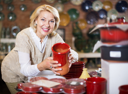Smiling senior woman posing with ceramic tableware at workshop