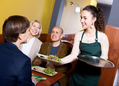 middle class: Sonriendo gente de clase media que disfruta de la comida, camarera feliz teniendo orden. Centrarse en la camarera