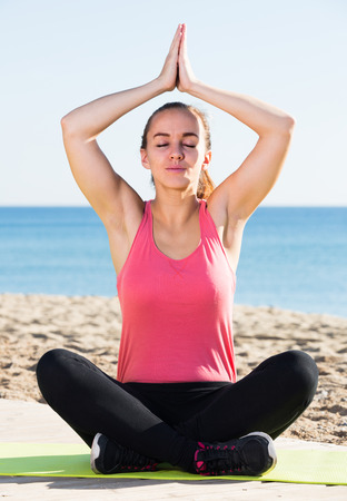 Cheerful young woman doind meditation in beach Stock Photo