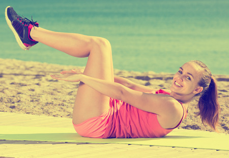 perspire: Beautiful adult sporty woman exercising at sea beach Stock Photo