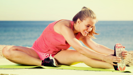 sportwoman: Cheerful young sportwoman workout  at sea beach outdoor Stock Photo