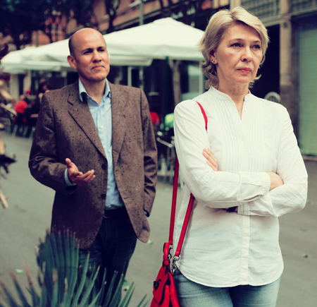 Portrait of annoyed mature woman standing away from arguing man outdoors Imagens