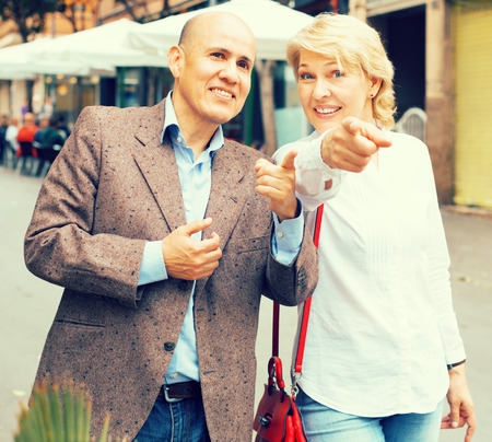 Portrait of smiling mature couple walking and pointing fingers in town