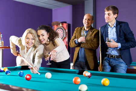 Group of friends playing billiards and smiling in night club. Focus on the women