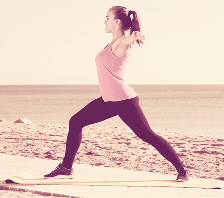 perspire: attractive girl exercising on exercise mat outdoor at the seaside Stock Photo