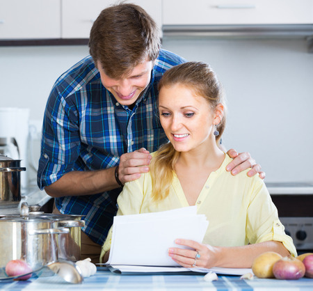 Positive adult spouses signing  forms for investment papers