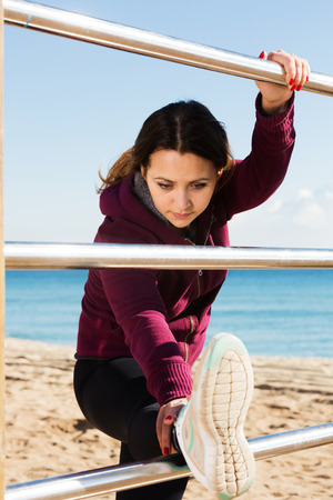 perspire: Portrait of glad young woman strerching at beach Stock Photo