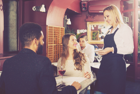 middle class: Positive young spouses having date in middle class restaurant