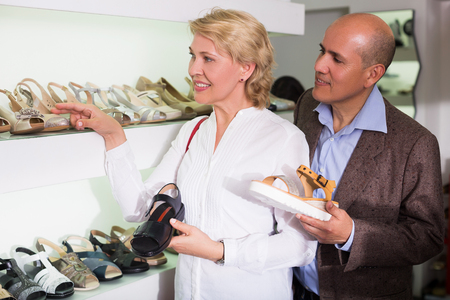 pensioner: Happy pensioner couple choosing casual shoes in store
