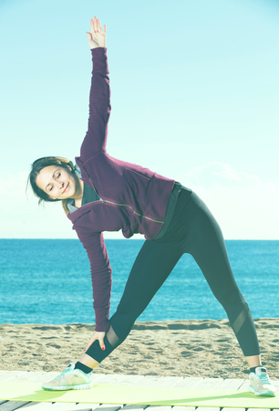 perspire: Happy girl exercising on exercise mat outdoor Stock Photo