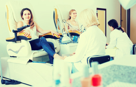 30s: Female clients 30s doing toenails in nail salon in afternoon Stock Photo