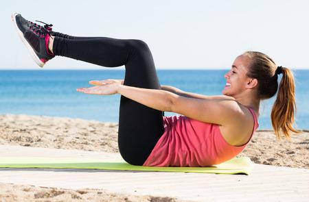 sportwoman: Cheerful young sportwoman training  at sea beach Stock Photo