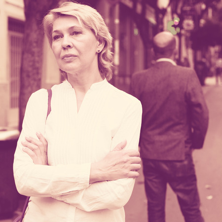 argumentation: Portrait of annoyed mature woman standing away from man standing back to her