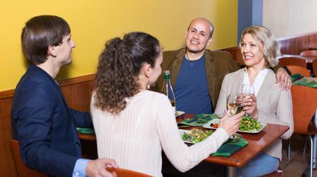 middle class: la gente alegre clase media agradables disfrutando de la comida y el vino en el café Foto de archivo