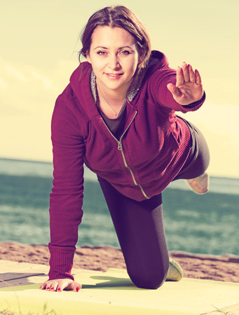 Portrait of positive young woman working out at seaside