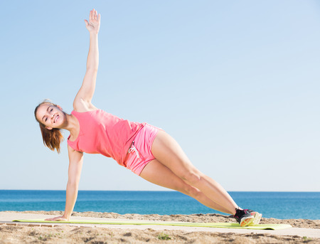 perspire: Happy adult sporty girl exercising at sea beach Stock Photo