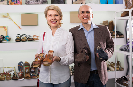 Two happy spanish retirees together choosing pair of shoes in fashion store
