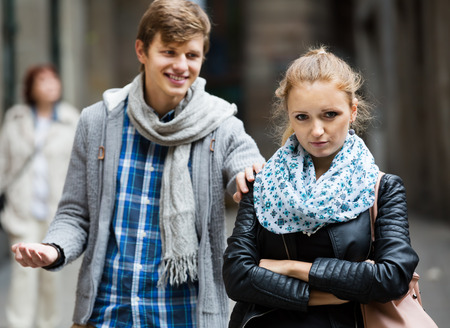 accosting: Young couple having quarrel on city street in an autumn day Stock Photo